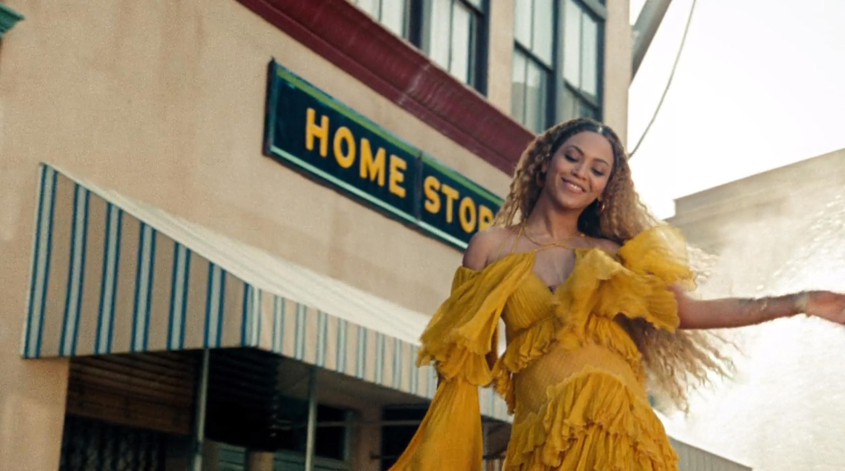 still of Beyoncé from the video from Hold Up, in which she destroys a surveillance camera and various other things while wearing the most beautiful yellow dress in the world